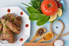 Fried chicken legs and wings, tomato, chili pepper, lemon, herbs, spices on wooden spoon on blue table. Served table with fried chicken legs and wings, tomato Stock Photography