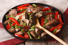 Fried chicken liver with peppers close-up on a dish. horizontal Royalty Free Stock Images