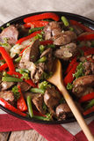 Fried chicken liver with peppers close-up on a dish. Vertical Royalty Free Stock Photo