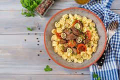 Fried chicken liver with tomato and garnish of pasta. Top view royalty free stock photo