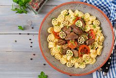 Fried chicken liver with tomato and garnish of pasta. Top view royalty free stock photography