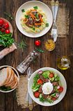 Fried chicken liver with vegetables and garnish of mashed potatoes. Warm salad from chicken liver, radish, cucumber, tomato and egg poached.  Served table Royalty Free Stock Photography
