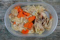 Fried chicken meat with red carrot pieces in a plastic plate. On a gray table stock photo
