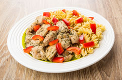 Fried chicken meat with spiral pasta and sweet pepper Stock Photos