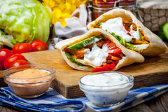 Fried chicken meat with vegetables in pita bread Stock Images