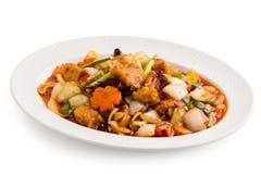 Fried Chicken mit Acajounüssen in der weißen Platte lokalisiert auf Weiß Lizenzfreies Stockfoto