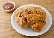 Fried Chicken mit Soße auf einem weißen Teller Stockbild