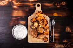 Fried chicken next to grilled squashes, sweet potatoes and sour cream souce. In a glass bowl on a wooden table stock photos