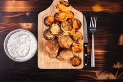 Fried chicken next to grilled squashes, sweet potatoes and sour cream souce. In a glass bowl on a wooden table stock image