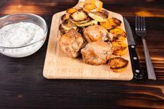 Fried chicken next to grilled squashes, sweet potatoes and sour cream souce. In a glass bowl on a wooden table royalty free stock photography