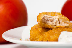 Fried chicken nuggets on plate with tomatoes Royalty Free Stock Images
