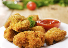 Fried chicken nuggets on the plate on the wooden table Royalty Free Stock Photos