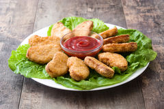 Fried chicken nuggets on wood. En table royalty free stock image