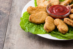 Fried chicken nuggets on wood. En table stock photo