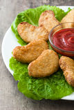Fried chicken nuggets on wood. En table royalty free stock photography