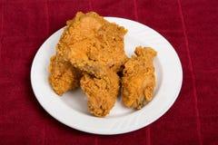 Fried Chicken op Kleine Witte Plaat en Rode Handdoek Stock Afbeelding