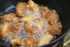 Fried chicken in a pan with hot oil. Golden yellow fried chicken in a pan royalty free stock photography