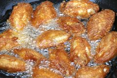 Fried chicken in a pan with hot oil. Golden yellow fried chicken in a pan royalty free stock photo