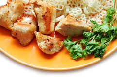 Fried chicken, pasta and parsley on orange plate Stock Photography
