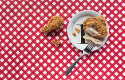 Fried chicken on plate with fork on red checkerboard tablecloth with copy space. Fried chicken on plate with fork on red checkerboard tablecloth horizontal Royalty Free Stock Images