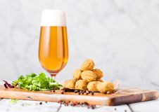 Fried chicken popcorn with fresh salad and beer. Fried crispy chicken popcorn with fresh salad and glass of beer on chopping board on wooden background Stock Photo
