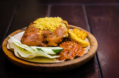Fried Chicken. A portion of fried chicken deliciously served along with some vegetables and sambal belacan, a hot sauce made from chillie Royalty Free Stock Photos