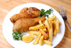 Fried chicken with potato. Fried chicken legs with lemon and potato served on the white plate Royalty Free Stock Photography