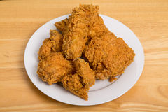 Fried Chicken quebradizo en la tabla blanca de la placa y de madera Foto de archivo