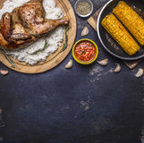 Fried chicken with rice on a cutting board, hot sauce, spices, garlic and corn in the pan on dark blue wooden rustic background to Stock Photo