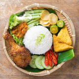 Fried chicken rice. Famous traditional Indonesian food. Delicious nasi ayam penyet with sambal belacan. Fresh hot with steam smoke royalty free stock images