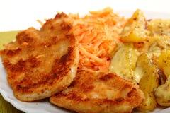 Fried chicken roasted potatos and carrot salad Stock Photos