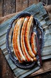 Fried chicken sausage on an iron plate, rustic style. Royalty Free Stock Images