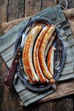 Fried chicken sausage on an iron plate, rustic style. Royalty Free Stock Photography