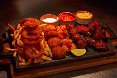 Fried Chicken Strips, alas de pollo, anillos de cebolla, palillos de pescados y patatas fritas compartiendo, Pune imágenes de archivo libres de regalías