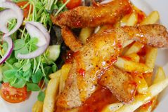 Fried chicken strips with chips and salad. Deep fried chicken strips drizzled with chilli sauce served with french fries and salad Stock Photography