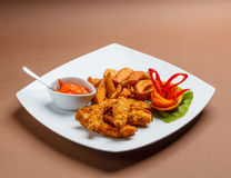 Fried chicken strips. With oven baked potatoes Royalty Free Stock Photo