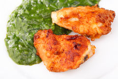 Fried Chicken Strips with spinach. Two Fried Chicken Strips with spinach puree Stock Photography