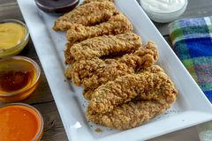 Fried chicken strips with variety of sauces. Fried chicken strips on white platter surrounded with various dipping sauces Stock Photos
