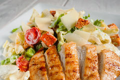 Fried chicken strips with vegetable salad close-up. Fried chicken strips with fresh vegetable salad close-up. Served caesar on white plate. Mediterranean cuisine Stock Photo