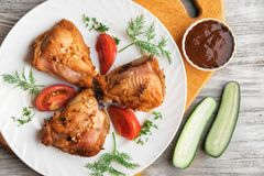 Fried chicken thighs and vegetables on a plate on a wooden background stock image