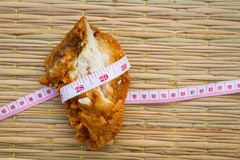 Fried chicken on traditional mat with measuring tape, diet conce Stock Image