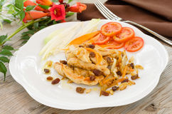 Fried chicken with various toppings. Dish of fried chicken topped with raisins,pine nuts and vegetables Stock Images