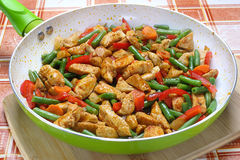 Fried chicken with vegetables. In frying pan Stock Images