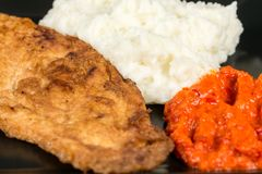 Fried chicken white meat with mashed potatoes and paprika ajvar on the black plate Stock Photo
