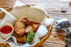 Fried chicken wing in the basket with chilli dipping sauce on the brown bark background decorated with sunglasses Royalty Free Stock Photography