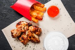 Fried chicken wings with baked potatoes and bbq sauce on craft paper on black background. Hot Meat Dishes. Top view royalty free stock photo