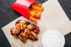 Fried chicken wings with baked potatoes on craft paper on black background. Hot Meat Dishes stock photos