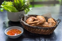Fried chicken wings in basket, and sweet and sour sauce with chili for chicken dip stock images