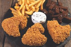 Fried chicken wings breaded crispy with french fries fried rye bread croutons beer snack Royalty Free Stock Photos