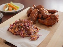 Fried Chicken Wings Covered i riktig varm BBQ-s?s med en sida av Cole Slaw Carrots och selleri tj?nade som p? en sk?rbr?da arkivbilder
